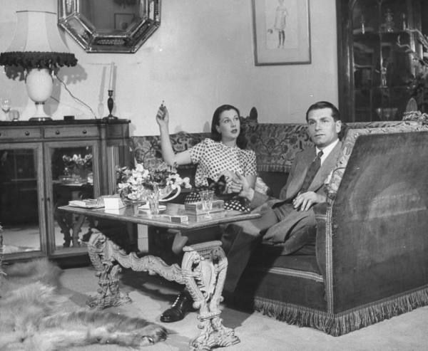 Actor Laurence Olivier relaxing w. his actress wife Vivien Leigh & their Siamese cat in living room at home. (London,1946)