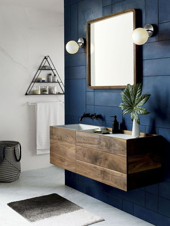 dark wood bathroom cabinet with drawers on a contrasting navy wall