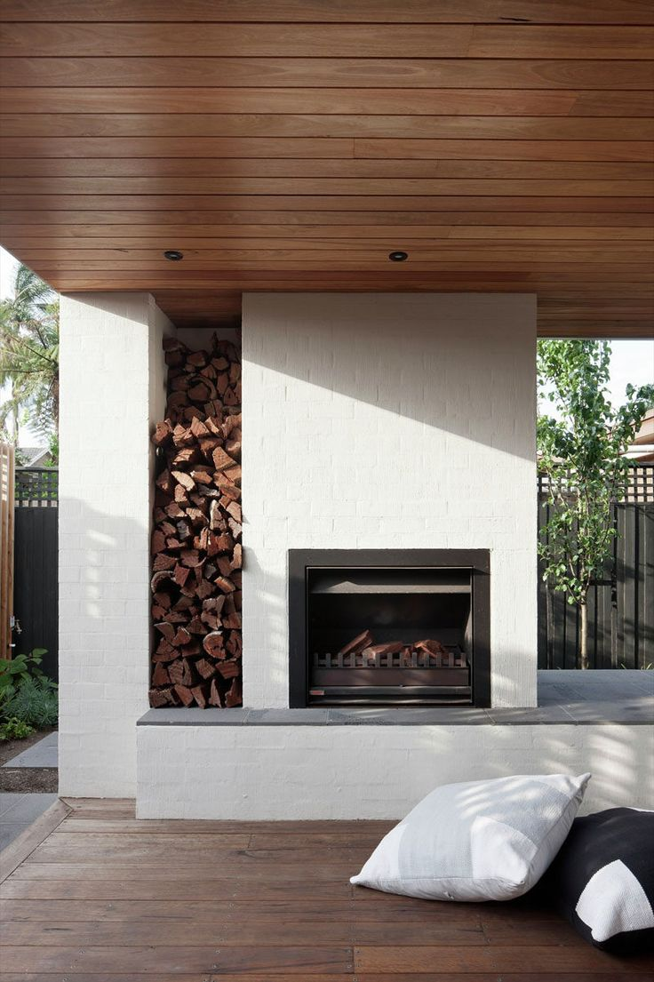 This outdoor fireplace is surrounded by brick that has been painted white. There's also a built-in space for firewood storage.