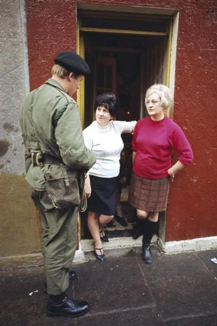 Second Lieutenant Nicholas Dixon, 1st Royal Green Jackets, talks to two Belfast women in their doorway during the Battalion's first tour of duty in Northern Ireland - 20 August to 18 December 1969
