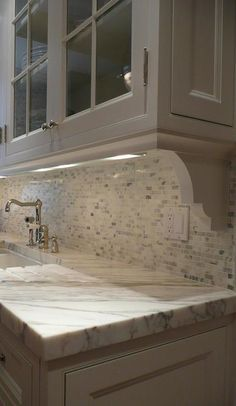 Close-up shot of white glass front upper cabinets with corbels over a mini marble mosaic tiled backsplash alongside a gray and white marble countertop which frames the kitchen sink with drainage grooves and hook spout faucet.