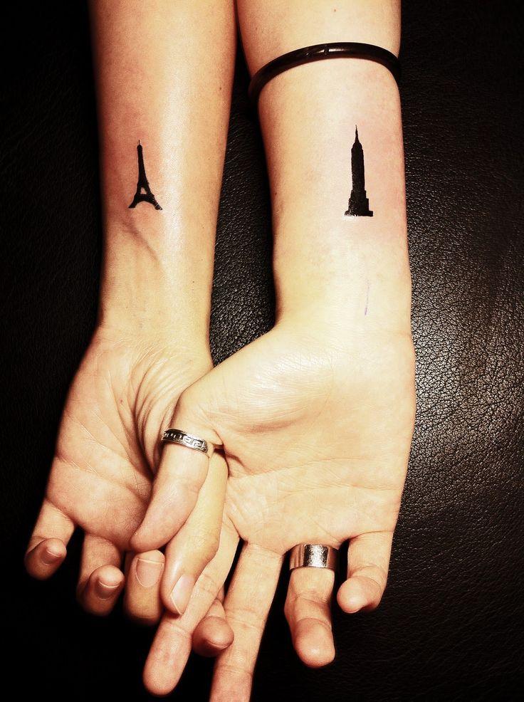 Pareja tomados de las manos mostrando sus tatuajes de paris