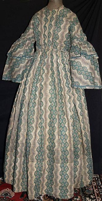 """1850s teal stripe challis dress. Deaccessioned from NY Museum.  Mostly hand sewn.  Pagoda sleeves trimmed in matching green ribbon and double ruching around armsycyes.  Piped at neck, waist & armcyes, bodice has original concealed hooks & eyes and is fully lined with cream linen & window pane linen, cartridge pleating on skirt, hem edged with green hem protector, right side pocket on skirt, skirt lined with floral calico.  Bust: 32""""; Waist: 28""""; shoulders across: 17""""; total length: 57"""" in back.: Window Panes, Green Ribbon, Eye"""