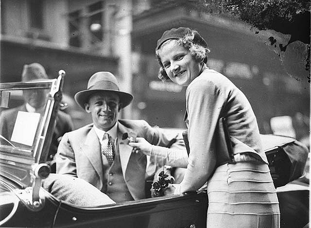 Poppy seller pins the flower on cricketer Don Bradman's lapel outside the State Theatre, Sydney, Remembrance Day, early 1930s / photograph by Sam Hood by State Library of New South Wales collection, via Flickr