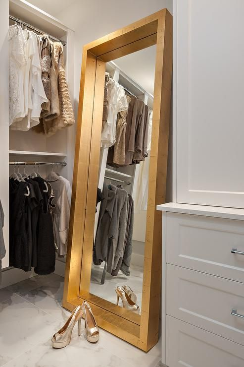 A gold full length mirror sits on marble porcelain floor tiles and leans against a wall between white built-in dresser and stacked clothing rails in a well appointed walk in closet.