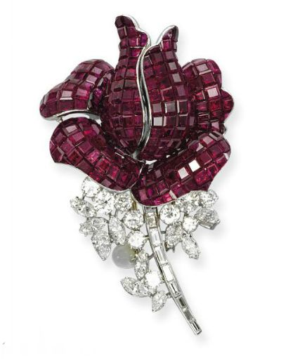 A RUBY AND DIAMOND FLOWER BROOCH   Designed as a rose, the petals set with calibré-cut rubies to the vari-cut diamond stylized leaves and baguette-cut diamond stem, 1960s, 7.0 cm long, with French assay marks for gold