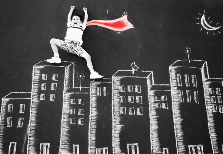 superman pose. Chalk photography with child posing standing on top of building with a cape.