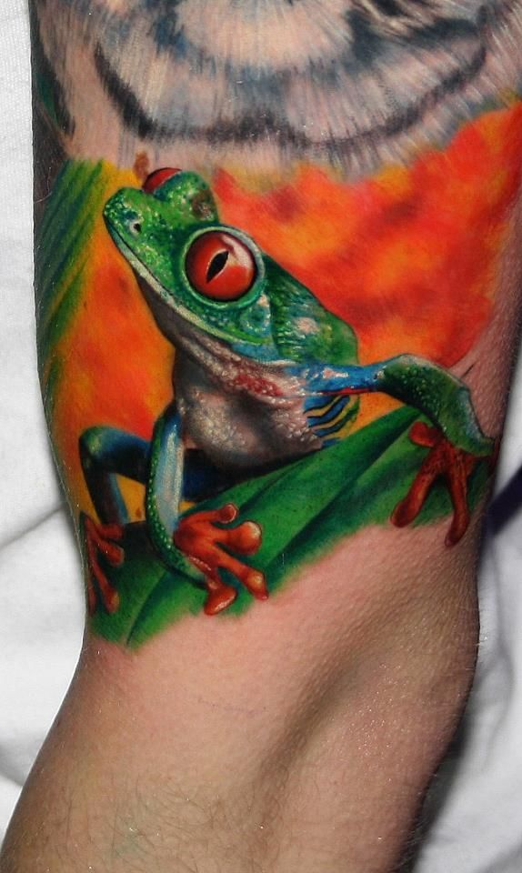 This bright, cute and colorful tree frog tattoo by Carlox Angarita is a bold body art statement for nature lovers.