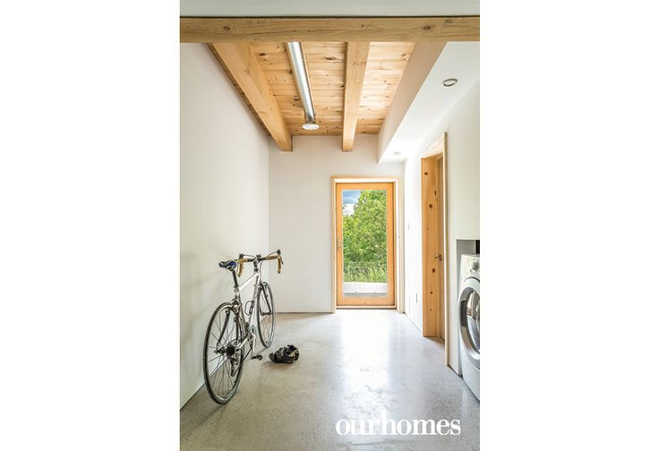 "The homeowners are avid cyclists. Laundry machines are tucked into the space under the stairs.     See more of this home in ""Prefab Scandi-Style Environmentally-Sensitive Home"" from OUR HOMES Southern Georgian Bay Mid-Summer 2016  http://www.ourhomes.ca/articles/build/article/prefab-scandistyle-environmentallysensitive-home"