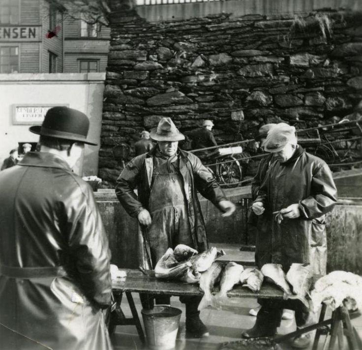 Fotografi av fiskehandlere på indre kai i Haugesund rundt 1950. Fisketorget var ennå i bruk utover på 1960-tallet. Senere overtok de mange fiskebutikkene all handel med fisk. Karmsunds folkemuseums store fotosamling trekker besøkende, både til museet og til Digitalt Museum. Foto: Karmsund folkemuseum, MHB-F.000616
