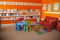 Cheery Greetings!  Tangerine walls and Cover-facing bookshelves.