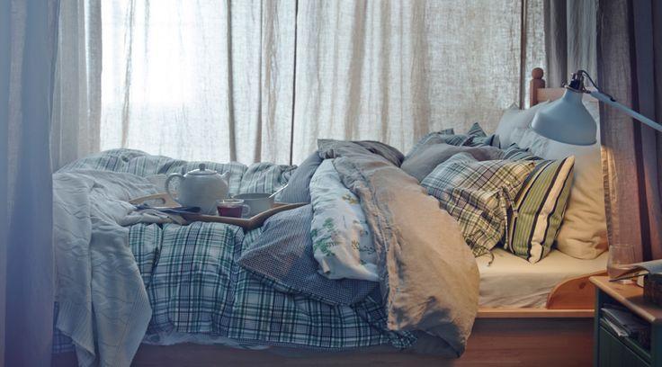 Letto con diversi piumini e trapunte, cuscini, biancheria da letto e tende.