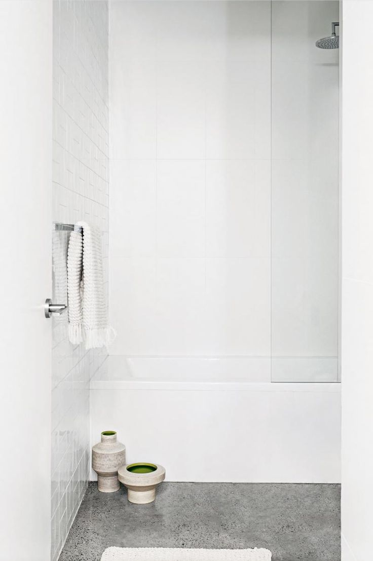 All-white bathroom, grey polished concrete floor, shower over bathtub