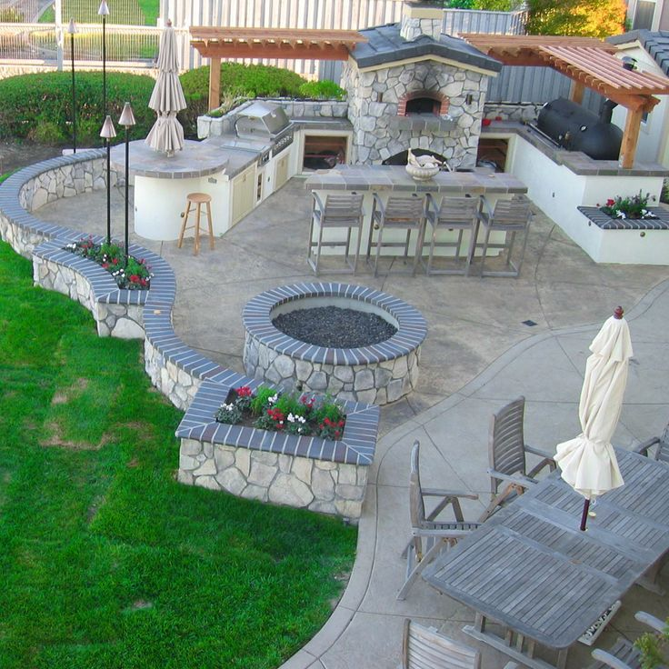 Outdoor kitchen space. Like how the area flows to one another, but needs seating around the fire pit
