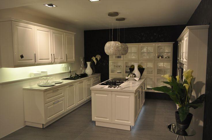 Landelijke keuken met vitrinekast. Deze landelijke keuken is voorzien van veel opbergruimte door de vele keukenkasten aan alle zijden van de muur. Het kookeiland vormt het middelpunt van de keuken.