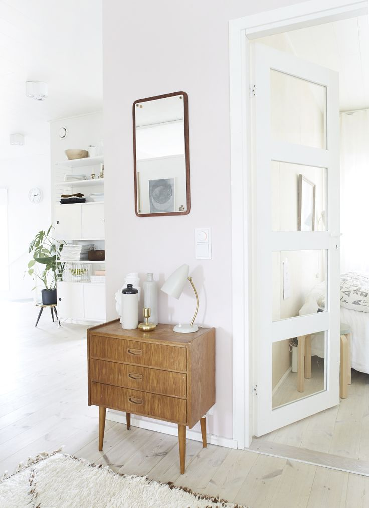 Bright white decor really lets the beautiful little mid century modern chest of drawers and mirror stand out!