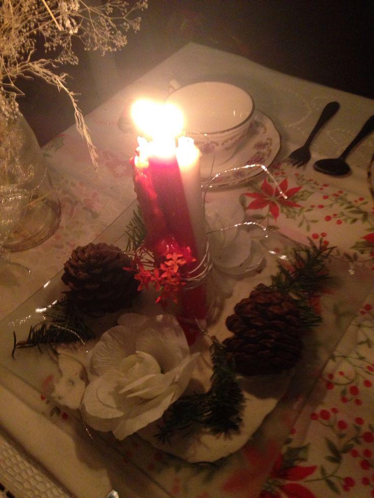 En un plato plano coloca arena, velas, castañas y naturaleza que resalte los colores navideños