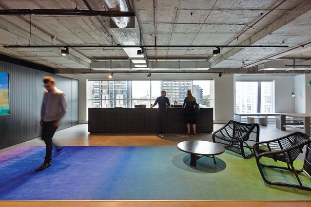 The reception area features a striking rug in gradated colours, which contrasts with the exposed concrete ceiling.