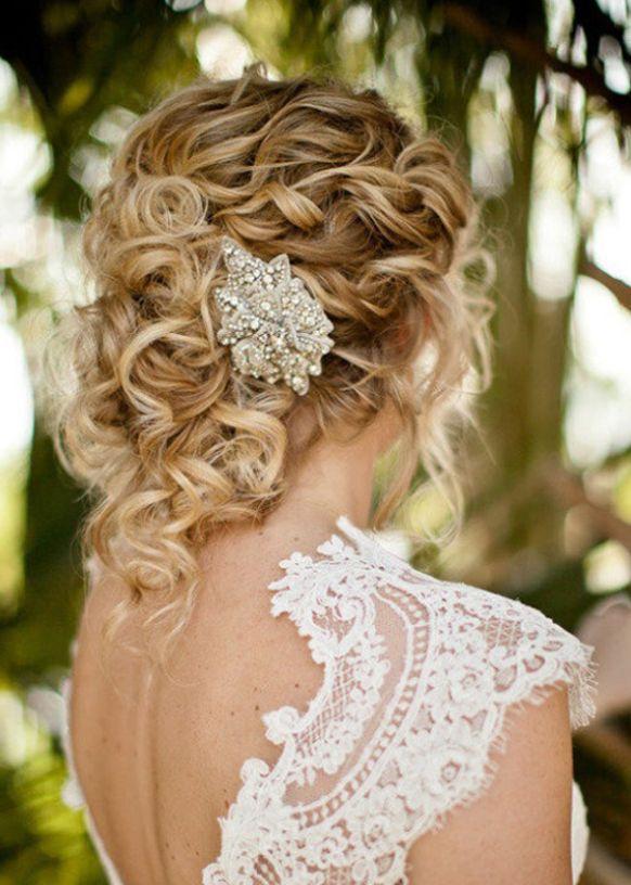 Cette mariée porte une coiffure superbe, tout en boucles. On remarque que le coiffeur a coiffé ses cheveux vers l'arrière et les a attachés pour former un genre de chignon très élégant, enjolivé d'un bijou scintillant. La coloration blonde est très réussie.