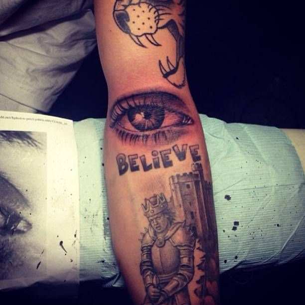 A Knight holding a sword tattoo on Justin's arm, below the realistic eye. Artista Tatuador: Bang Bang · Keith McCurdy