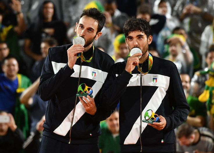 Italy's silver medallists Paolo Nicolai and Daniele Lupo celebrate on the podium at the end of the men's beach volleyball event at the Beach Volley Arena in Rio de Janeiro on August 19, 2016, during the Rio 2016 Olympic Games.  / AFP / Leon NEAL