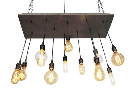 Handmade industrial chandelier. Includes a combination of 12 bulbs as pictured. Wood is stained a smoke color, black pendant wire, and solid brass sockets in a black finish.  ATTENTION: Designers, Contractors, Builders, etc. This light is perfect for any commercial space, and will pass any inspection! SPECS Base: 12 x 35 Stain: Smoke Sockets: Black Cord: Black Pendants: 12 - Longest bulbs hangs 27 from base. Bulbs: 12 included as shown Use: Dry location only  UL listed: YES  INTERNATIONAL…