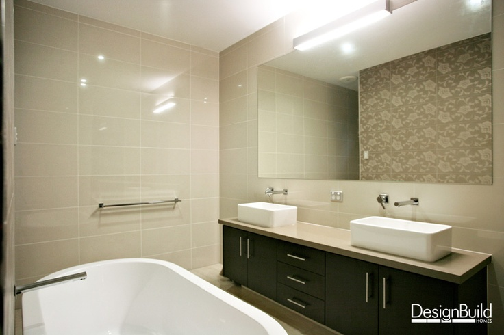 Bathroom with freestanding bathtub, his and her vanities and feature wallpaper.