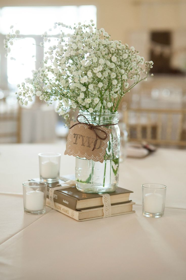 Simple, rustic centerpiece using old books, mason jar vases, Baby's Breath, and candles from our wedding. Copyright – Jerdan Photography