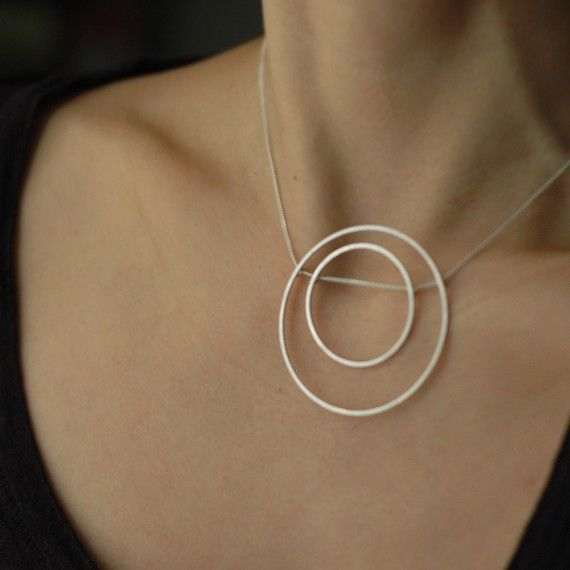 Simply bold, contemporary and kinetic to boot!  Hand fabricated from scratch out of solid sterling silver, both the pendants are made in a way so it rolls along the chain as you move. the smaller circle may move a little to the right or left depending on your movements. This is a fun designer piece, classic and yes... Oh so tempting.    The square solid sterling silver wire pendants have been forged for strength to avoid bend-ability. The solid sterling silver chain can be worn at…