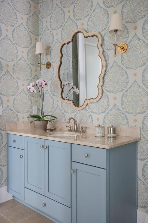 Chic blue powder room features a blue shaker washstand topped with cream stone fitted with a round sink and satin nickel faucet placed under a cream bone ...