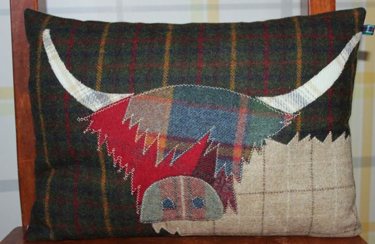£65.00 Beautiful handmade Highland Cow cushion, filled with a feather pad. This particular Coo is appliquéd onto a rich dark green & gold tartan background. His body is a cream /chocolate check. The shaggy fringe is muted greens and blues which flops over a scarlet red face. Topped off with stunning longhorns in grey & caramel.