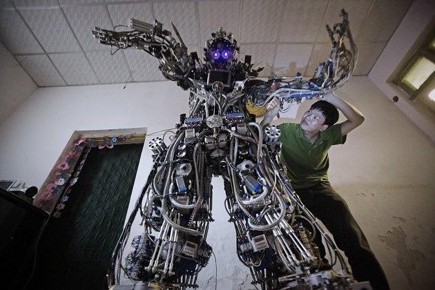 CHINE, Pékin. L'inventeur chinois Tao Wiangli modifie les circuits électriques de son robot, le 15 mai 2013. Agé de 37 ans, Tao a dépensé environ 150 000 yuans (25 000 dollars) et travaillé 11 mois pour construire son robot composé de ferraille. Son oeuvre mesure plus de 2 mètres et pèse 480 kg