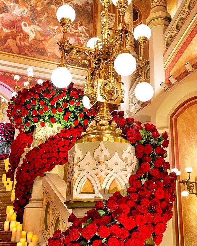 The inspiration continues! We love this #detail shot of Jeff Leatham's dramatic red rose and candle-adorned staircase. | WedLuxe Magazine | #wedding #luxury #weddinginspiration #floral #floralbackdrop