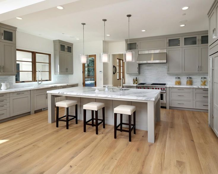 This minimalistic kitchen features gray Shaker cabinets, marble countertops and a neutral mosaic backsplash. Three glass pendant lights hang above the spacious island, which mirrors the cabinet and countertop design seen throughout the kitchen.