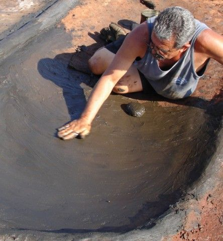 Frank Santos applying the clay to make a punee (bed) where the salt from ocean water will crystallize. Photo courtesy Kuulei Santos (Article describing the process of Hawaiian salt making at Salt Pond Beach, Kauai)