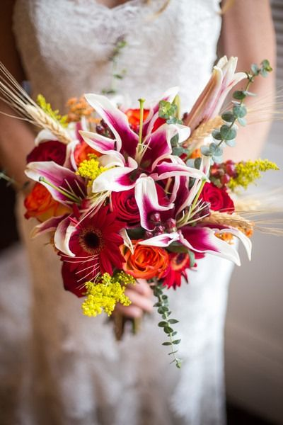 Fall wedding bouquet idea - pink, orange + red bouquet with gerber daisies, stargazer lilies, goldenrod, wheat and eucalyptus {Jessica Ryan Photography}