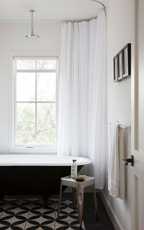 black tub, white curtains & walls, pictures on the wall, graphic tiles