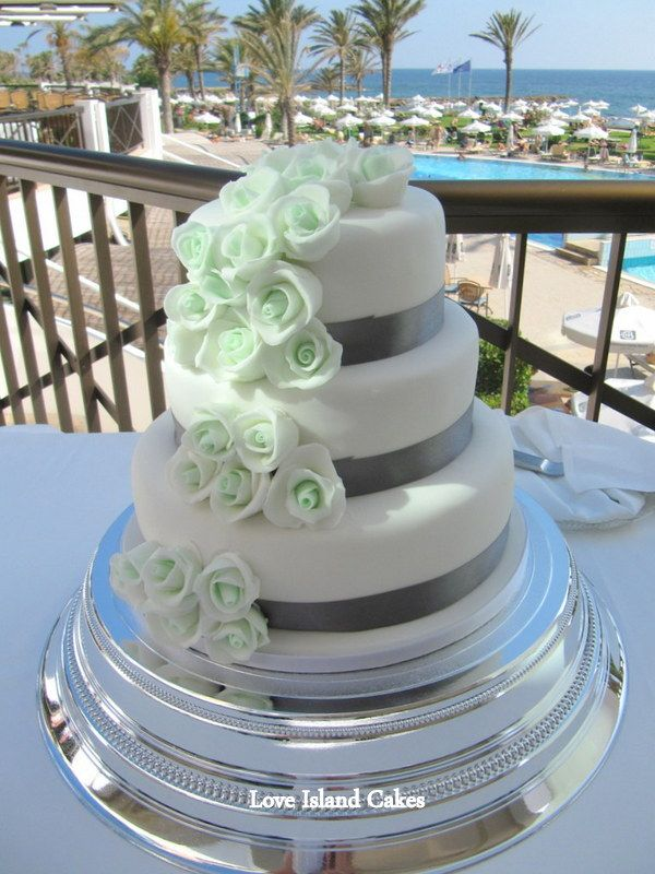 MINT ROSE WEDDING CAKE  Three tier white cake with a cascade of mint sugarpaste roses and charcoal ribbon