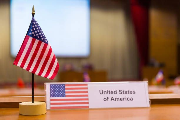 united states of americas small flag on meeting table with blurred
