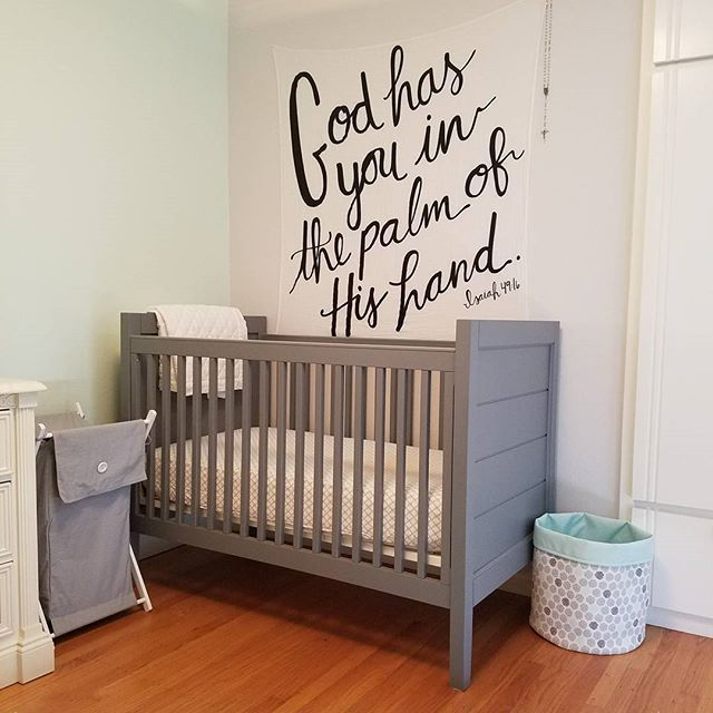 A cozy and sweet gender neutral nursery. Replicate this cute baby room with Pottery Barn grey crib and Modern Burlap's scripture swaddle blanket as a wall hanging.