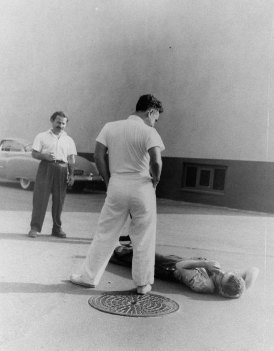 Elia Kazan and Nick Dennis observe James Dean's unconventional way of relaxing around the studio set.