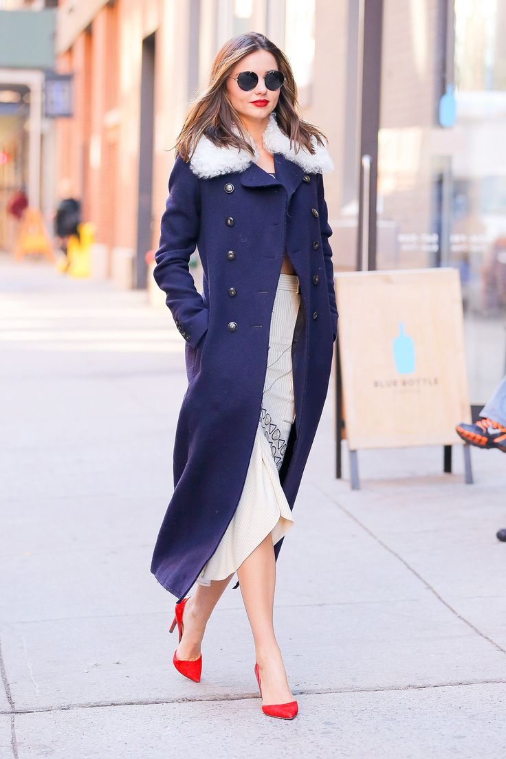 Miranda Kerr wears a Sonia Rykiel navy coat, a white dress, and red suede pointed-toe heels