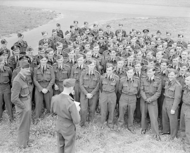 Royal Air Force 1939-1945- Bomber Command Watched by the CO, Wing Commander D A Gardner (left), aircrew of No 166 Squadron at Kirmington, Lincolnshire, gather on 20 July 1944 to hear the Adjutant, Flight Lieutenant F C Tigh, read out a congratulatory message from Field Marshal Montgomery, thanking the bomber crews for their efforts supporting the British Second Army's armoured offensive in Normandy, Operation 'Goodwood', 20 july 1944.