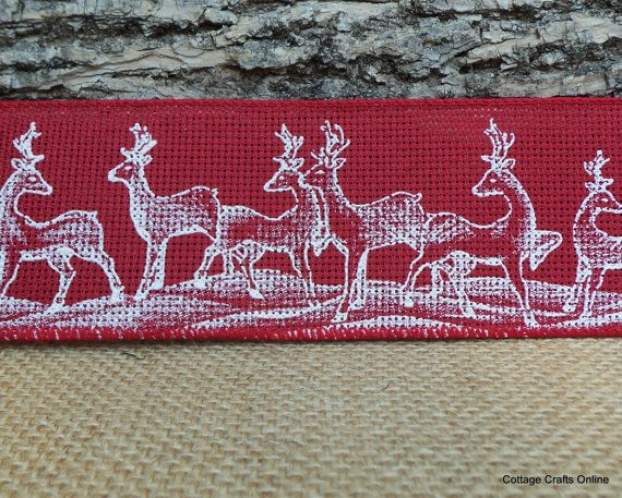 White deer print on a crimson red poly burlap style ribbon with an airy weave and a wired edge from high end boutique ribbon producer d. stevens. From the Cottage Crafts Online shop on Etsy.