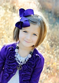 Cute little girl with bobbed hair with purple bow