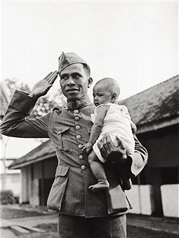 An Indonesian soldier who has enrolled in the Duch army holding his little child in his arms. Dutch East Indies (Indonesia), March 1940 - pin by Paolo Marzioli