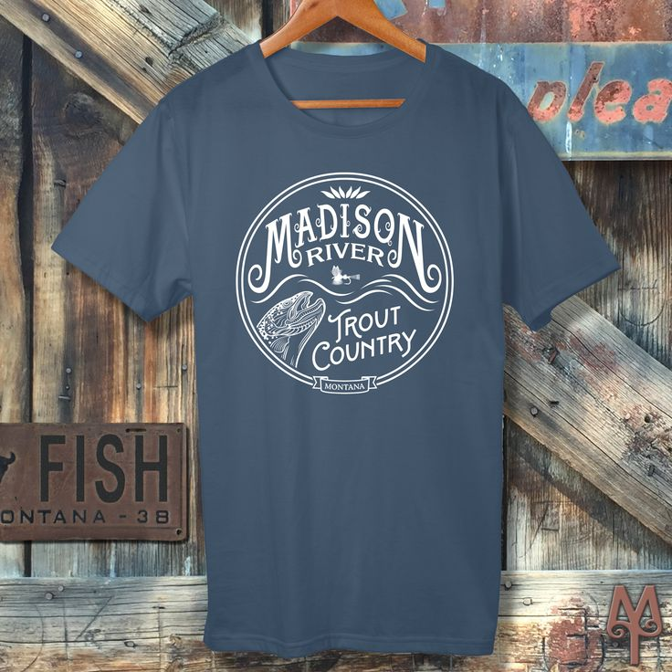 A New Steel Blue 'Madison River Trout Country' T-Shirt hanging on a vintage barn door in Nevada City, Montana