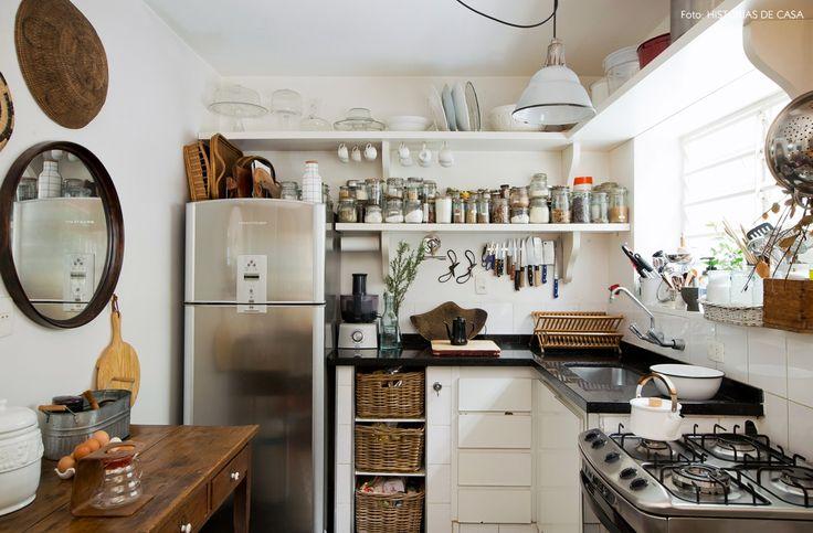 Cozinha simples e integrada conta com prateleiras abertas e cestas de vime para organização.