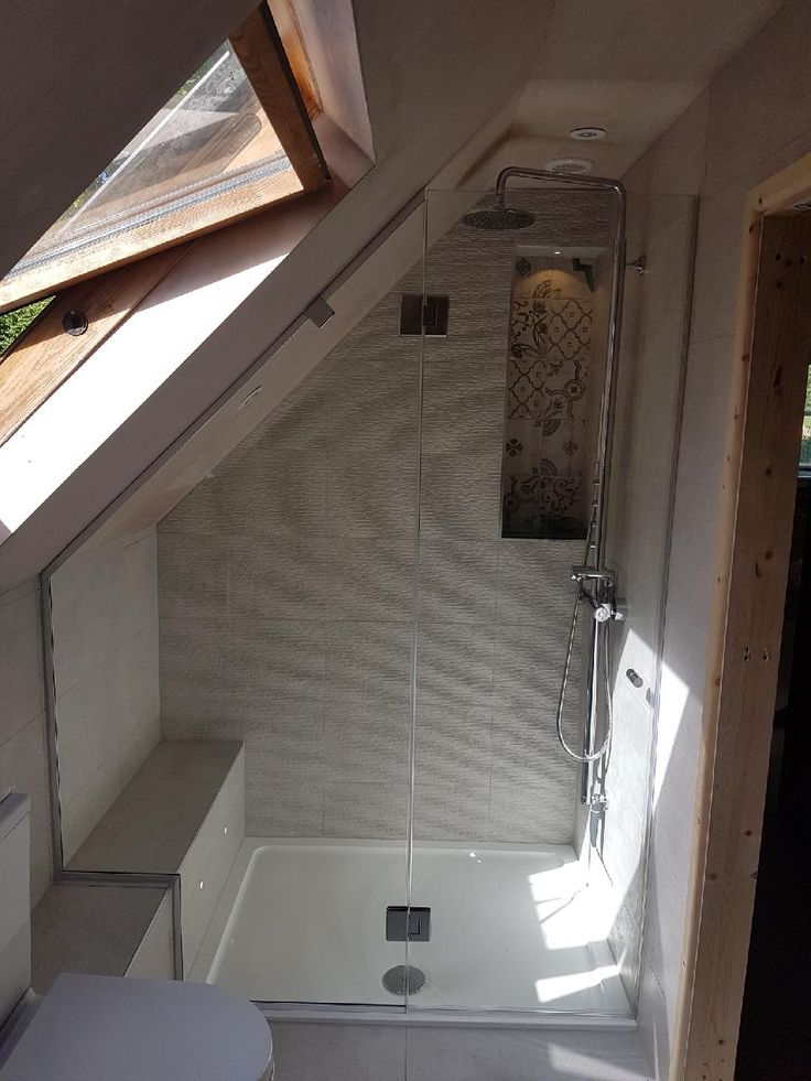 Loft shower enclosure installed over seat near Win…
