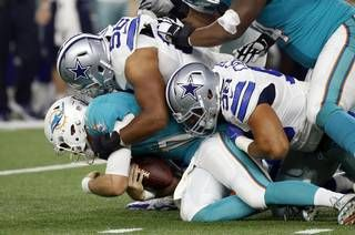 Miami Dolphins quarterback Ryan Tannehill is sacked by Dallas Cowboys' Jack Crawford (58) and Tyrone Crawford (98) in the first half of an NFL preseason football game, Fri., Aug. 19, 2016, in Arlington, Texas.